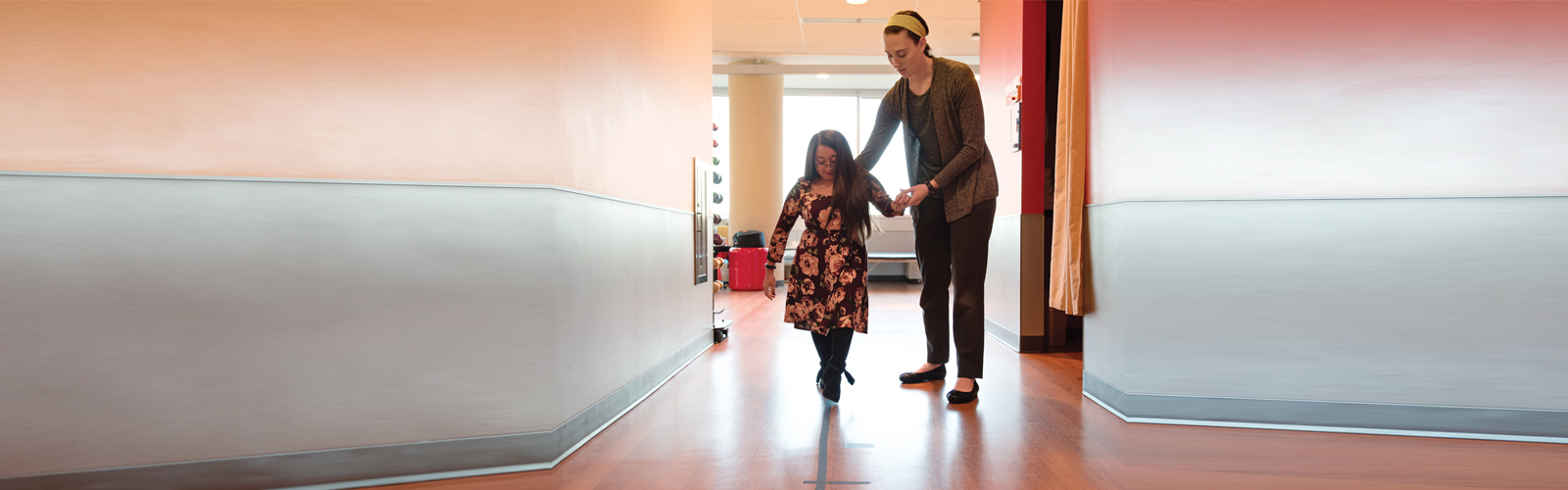 Shannon and her therapist walk down a corridor at Kennedy Krieger
