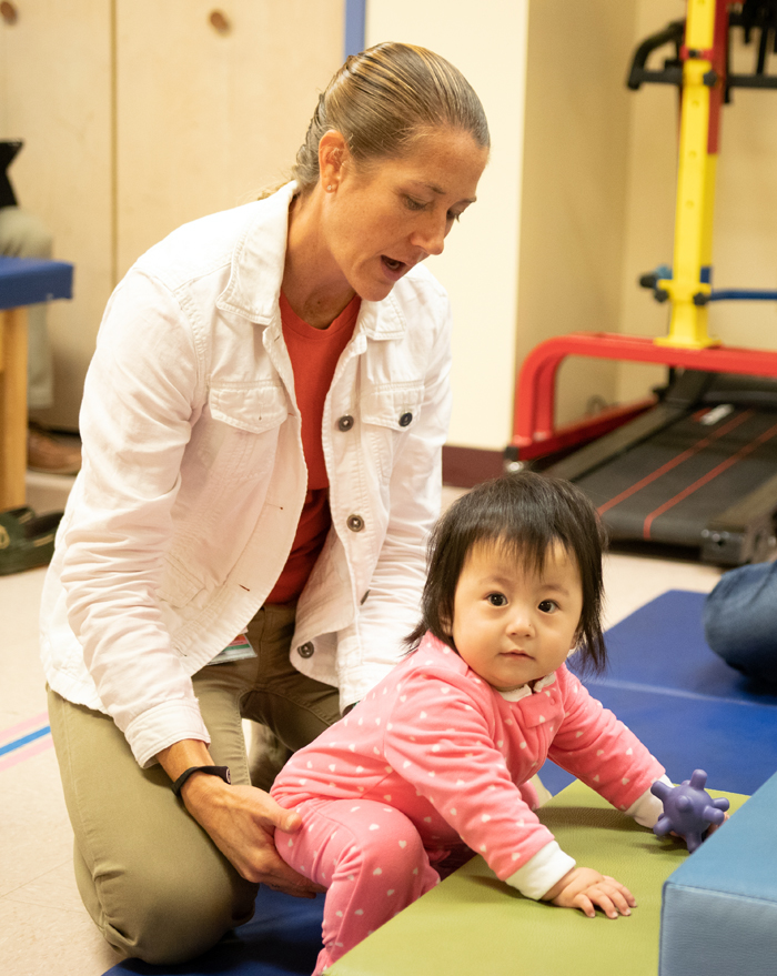 A young patient looks at the camera while a physical therapist holds her leg during a therapy session.
