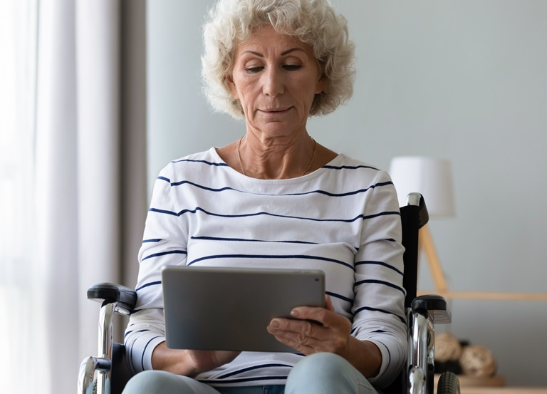 A female patient using a wheelchair holds a tablet in her home