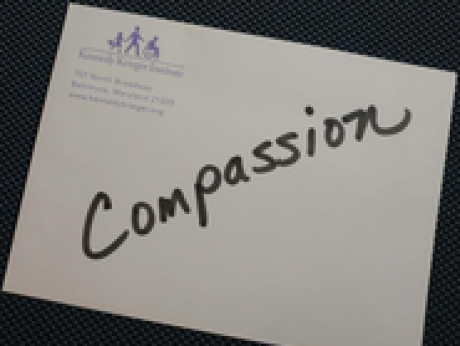 "A piece of paper with the word ""Compassion"" written across it in black"