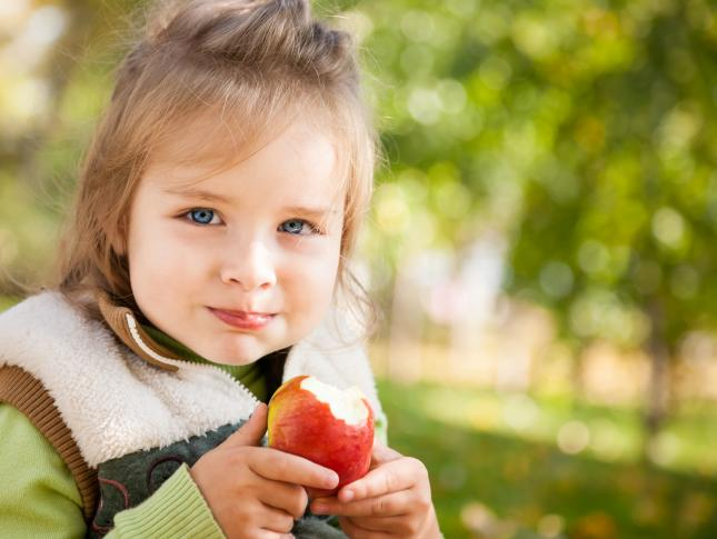 A young girl is holding an apple she has taken a bite out of while sitting outside