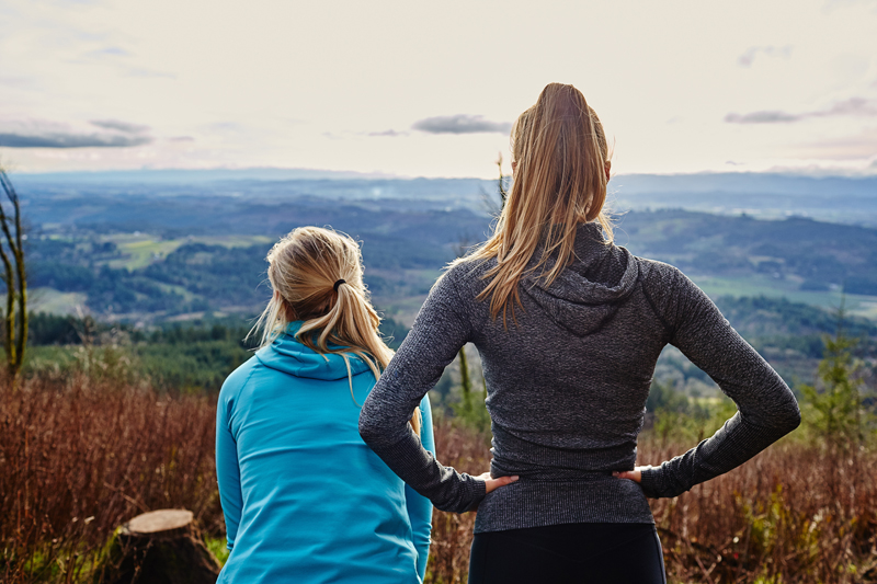 Two women with their backs to the camera look out over a mountain