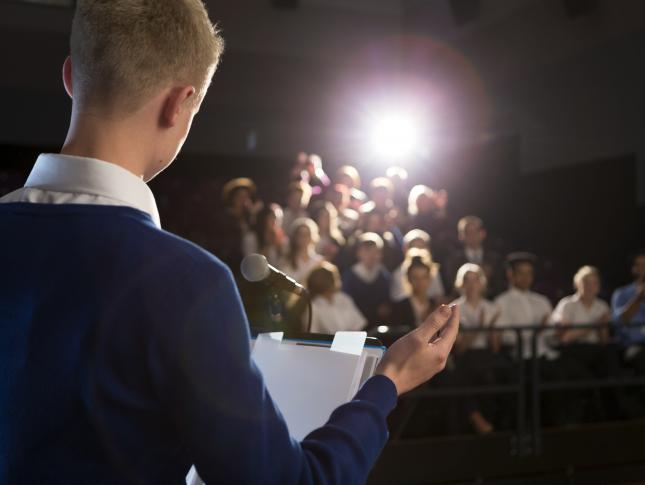 A photograph of a boy standing on a stage and presenting to an audience
