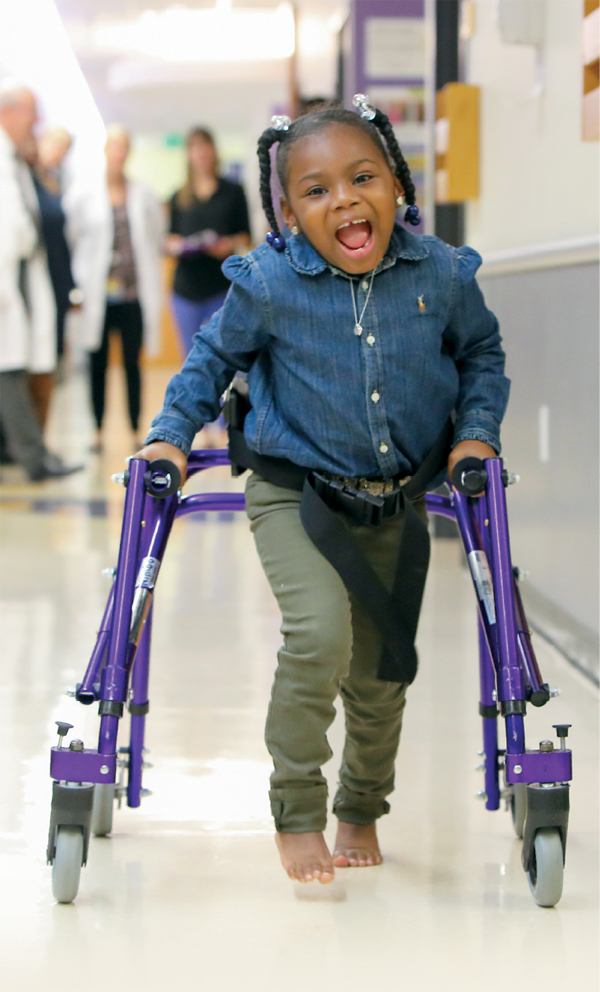 A photo of Journee walking down a hallway at Kennedy Krieger while using her walker.