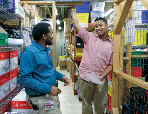 A photo of John Perry talking to Shawn Fallin, a fellow inventory technician who serves as John's mentor.