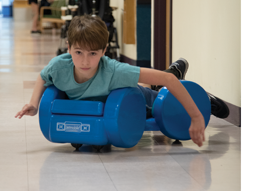A photo of Brayden mock-surfing down the hall at the Institute's day hospital.
