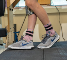 A photo of Brayden's legs as he uses a Bioness device while walking on a treadmill during physical therapy at Kennedy Krieger. The device delivers functional electrical stimulation to Brayden's right leg to improve his gait.