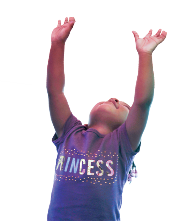 A young girl looks up and holds her hands in the air.
