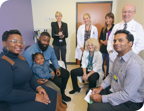 A photo of Journee with her parents, Ebony and Antwonn, and medical team members (left to right, back to front) Dr. Hilary Gwynn, Colleen Lenz, Dr. Sarah Korth, Dr. Shenandoah Robinson, Dr. Frank Pidcock and Dr. Ranjit Varghese.