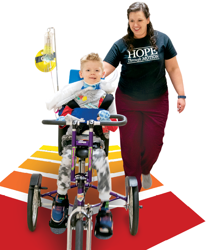 A photo of Geuko riding a tricycle with physical therapist Dr. Courtney Porter.