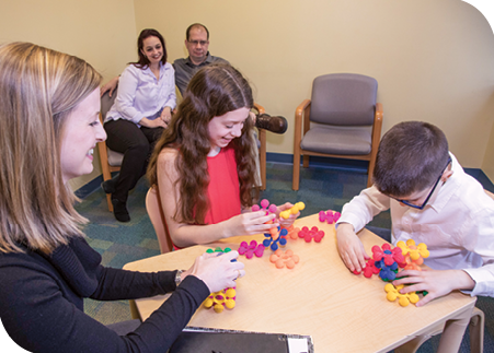 Dr. O'Donnell leads Reagan and Thomas in a creative activity during a therapy session, while Amanda and Todd look on.