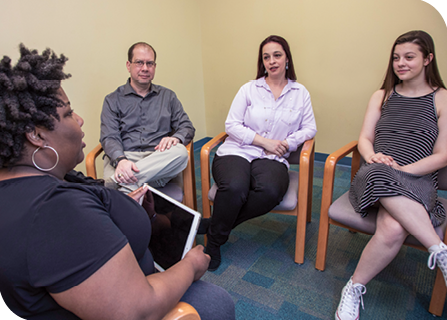 Dr. Christi Culpepper (left) talks with Addison (right) and Addison's parents, Todd and Amanda (center), during a therapy session.