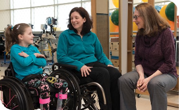 Pediatric nurse practitioner Janet Dean (right) talks with Caetlyn and her mom, Caryn, both patients at the Institute's International Center for Spinal Cord Injury.
