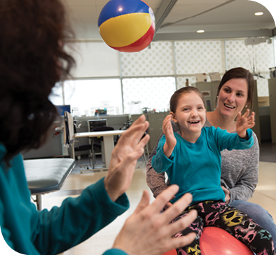 Physical therapist Lizzie Neighbors (right) helps Caetlyn balance on a therapy ball while Caryn and Caetlyn toss a beach ball back and forth during physical therapy.
