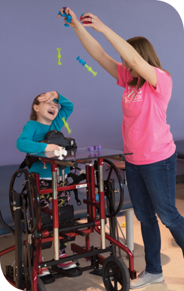 Physical therapist Brooke Meyer (right) drops suction cup toys on Caetlyn during physical therapy at Kennedy Krieger. A stander supports Caetlyn in an upright position.
