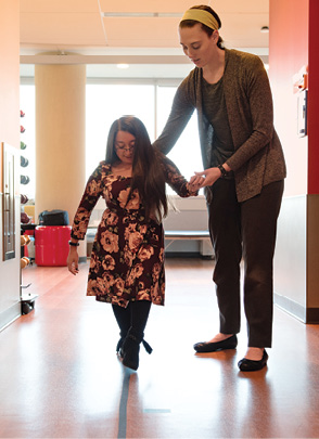 Shannon practices walking on a straight line with physical therapist Marianna Kogut.