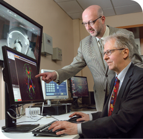 Dr. James Pekar (standing) and Dr. Peter van Zijl watch a brain scan in process.