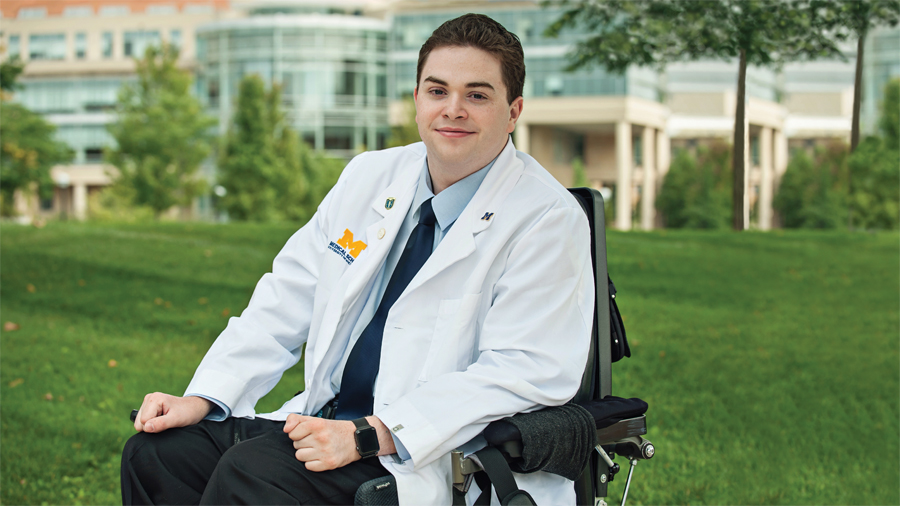 Chris Connolly poses wearing his University of Michigan Medical School white coat.