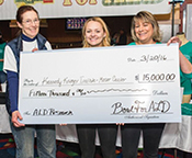 Ann Moser with Taylor Kane, and her mom, Diane Kane, as they present a check for ALD research