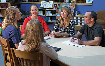 Staff members at Kennedy Krieger's Fairmount school, which Mikey attended for more than five years, sit around a table.