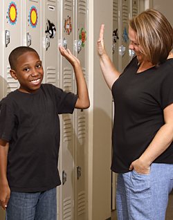 Mikey gives his teacher, Gabriela Bandi, a high-five in front of his locker at Kennedy Krieger High School.