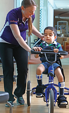 At Kennedy Krieger's outpatient center, physical therapist Brittany Hornby helps Karam ride a tricycle.