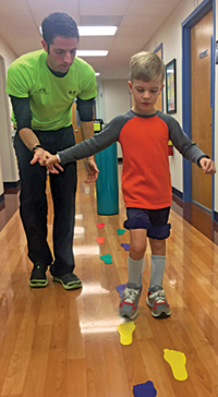 At Kennedy Krieger's outpatient center, Nathaniel practices walking with physical therapist Jason Benincasa.