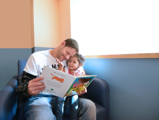 Patient Sanayah Pineiro sits with her dad as he reads her a book