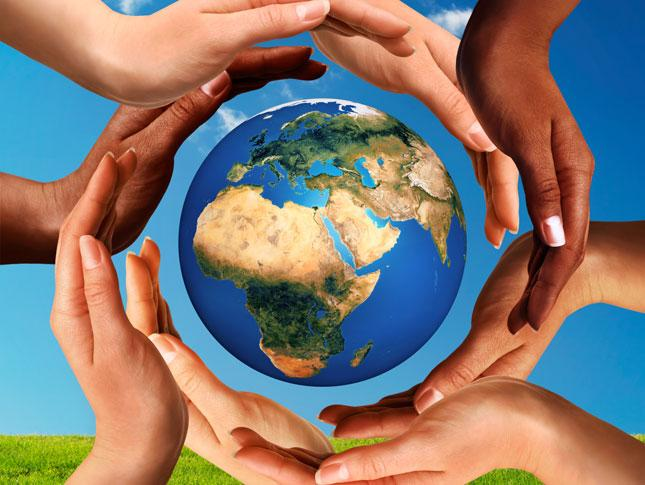 Multiracial hands making a circle together around the Earth.