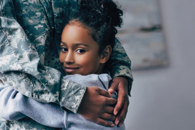 A young girl looks at the camera as she hugs an adult wearing a military uniform