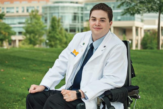 Chris Connolly poses wearing his University of Michigan Medical School white coat