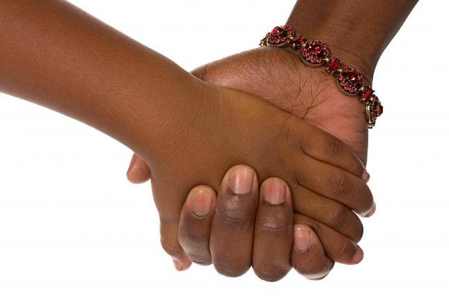 A photograph of a child's hand holding the hand of an adult