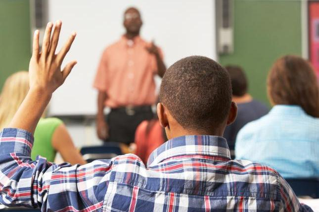 A photo of a student sitting in class, raising his hand and being called on by the teacher