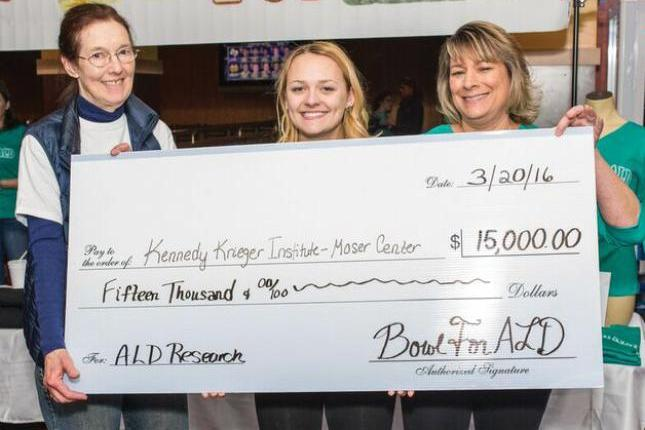 Taylor holds a check that shows the amount of money she has raised to support ALD research at Kennedy Krieger