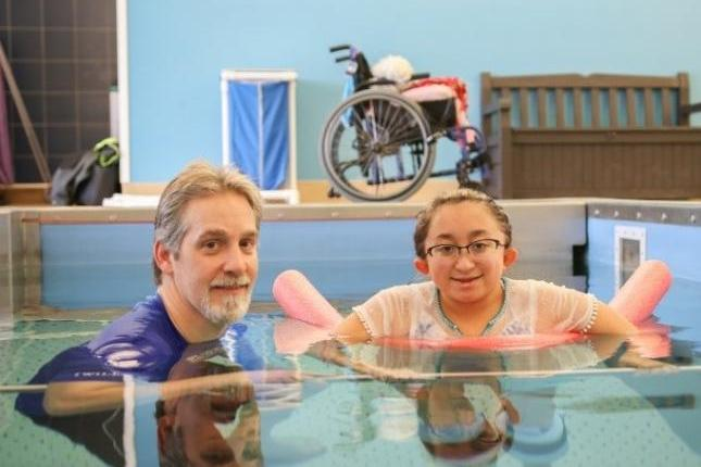 A photo of Shannon in an aquatic therapy pool with her physical therapist, Chris Joseph