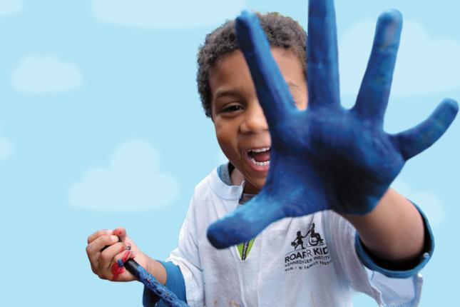 A child holds a paintbrush in his right hand while holding his left hand to the camera, with his palm covered in blue paint