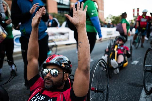 Handcyclists cross the finish line.