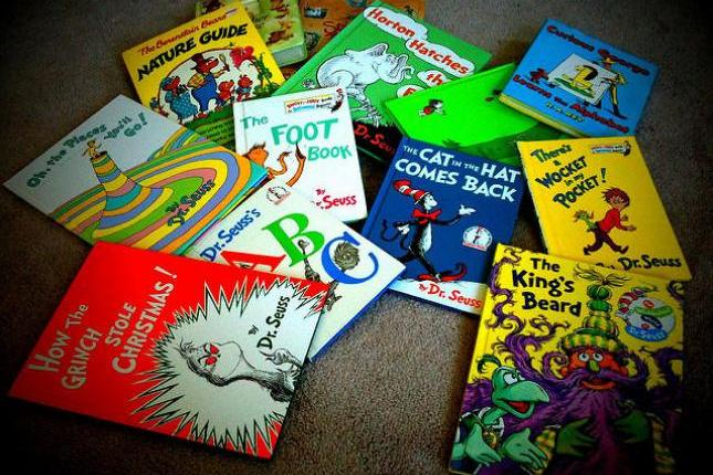 An assortment of Dr. Seuss books sit atop a carpet