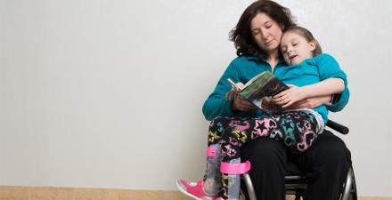 Caetlyn sits on Caryn's lap as she reads her a book.