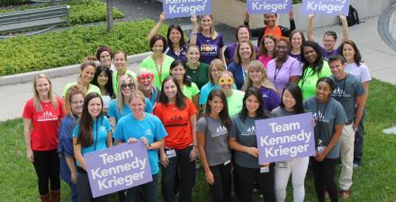 "A group of Kennedy Krieger employees, wearing Kennedy Krieger shirts and holding signs that read, ""Team Kennedy Krieger"""