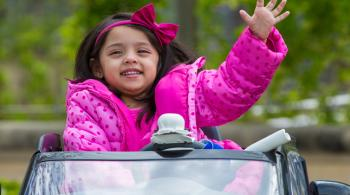 3-year old patient Sanayah waves from a modified car