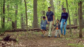 Pictured is Kennedy Krieger patient Dale walking through the woods as he holds hands with his mom, Gina, his dad, Gill, and his little brother, Myles.
