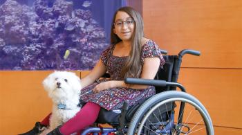 Frosty, Shannon's service dog, keeps Shannon safe when she's walking in public. Frosty makes sure no one bumps into Shannon, which could harm Shannon's bones. For longer distances, Shannon uses a wheelchair, with Frosty curled up in her lap or at her feet. In this picture, Shannon is sitting in her wheelchair, with Frosty sitting by her feet.