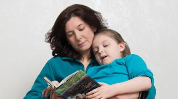 Caetlyn lays in her mom, Caryn's lap, as Caryn reads a book to her.
