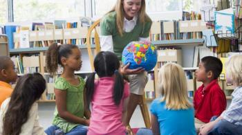 A photo taken in a classroom captures a teacher sitting in a chair and holding a globe and showing it to her students, sitting on the floor