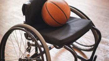 A photograph of a wheelchair with a basketball laying in the seat