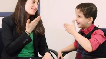 A therapist communicates with a hard of hearing patient using American Sign Language