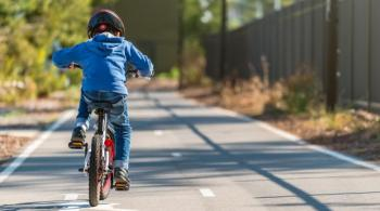 A photograph of a boy riding a bike along a sidewalk