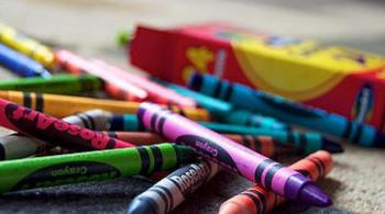 A photograph of crayons atop a rug, sitting next to the crayon box
