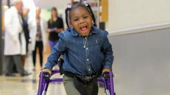 A photo of Journee in the hallway at Kennedy Krieger, smiling at the camera as she walks with the assistance of a walker
